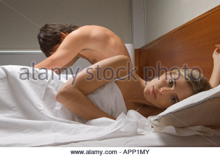 Couple ignoring each other in bed - Stock Photo
