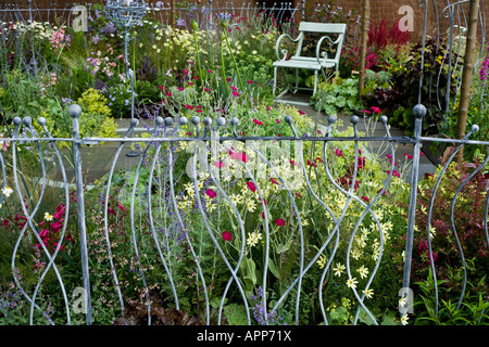Decorative ironwork railings on edge of small garden with seat and ironwork bird station behind. Long depth of field - Stock Photo