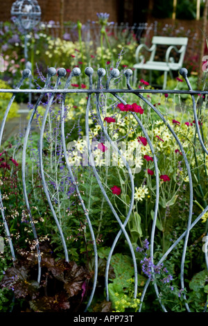 Decorative ironwork railings on edge of small garden with seat and ironwork bird station behind. Shallow depth of - Stock Photo
