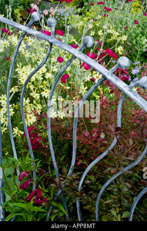 Decorative grey silver ironwork railings on edge of small garden with red, pink and yellow flowers behind - Stock Photo