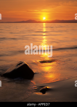 Sunset across Tremadog Bay from the beach on west coast. Llanfair Gwynedd North Wales UK Britain - Stock Photo