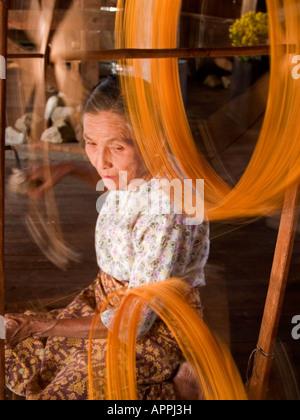 old woman weaving lotus threads into silk at Inle Lake in Myanmar - Stock Photo