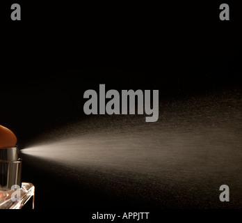 Spray aerosol against a black background - Stock Photo