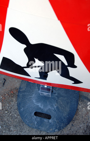 looking down high level view of a men at work roadworks sign in red and white warning triangle showing men working - Stock Photo