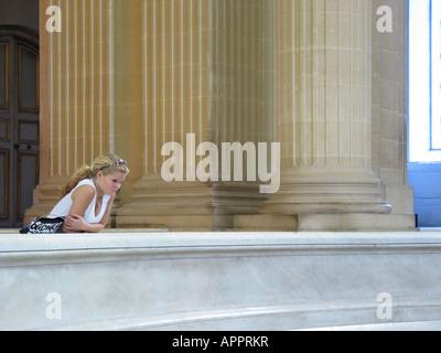 adolescent girl leaning against railing inside Dome Des Invalides Paris France - Stock Photo