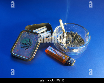 Ashtray with burning cigarette, lighter and cigarette box with cannabis leaf - Stock Photo