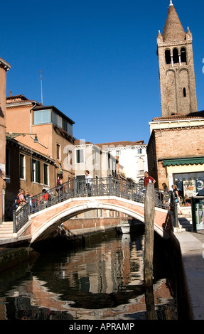 Pedestrians crossing a small bridge over a pretty canal in Venice, Italy with reflections. - Stock Photo