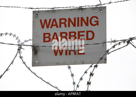 warning barbed wire sign attached to barbed and razor wire on top of a fence Belfast Northern Ireland UK - Stock Photo