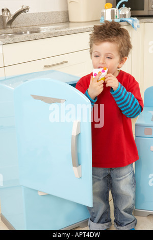 a boy plays in a kitchen with a toy fridge, he stands in its doorway whilst he pretends to eat a toy piece of cake. - Stock Photo
