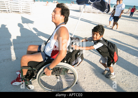 Miami Beach Florida public beach Hispanic boy pushes father wheelchair - Stock Photo