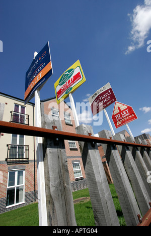 A row of estate agents signs outside newly built flats on the site of Swindon s historic GWR railway works - Stock Photo