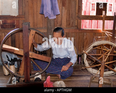 old woman spinning lotus threads into silk which is a cottage industry at Inle Lake in Myanmar - Stock Photo