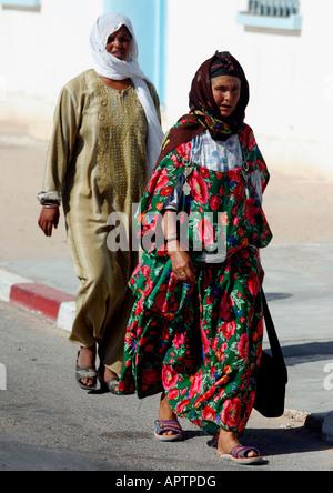 Two local women walking down the street in Kairouan, Tunisia. - Stock Photo