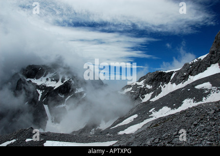 The Yulong (Jade Dragon) Mountain covered in snow and cloud. Yunnan, China. - Stock Photo