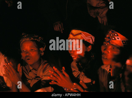 Bushwomen sitting at fire and singing Namibia - Stock Photo