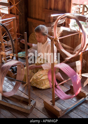 a woman sits spinning lotus threads into silk at Inle Lake in Myanmar - Stock Photo