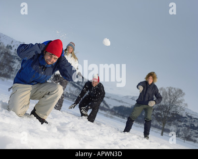 Friends throwing snowballs - Stock Photo