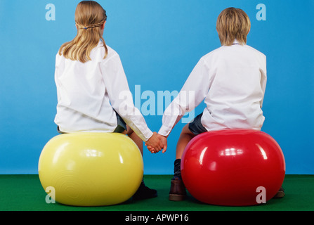 Girl and boy sitting on exercise balls holding hands - Stock Photo
