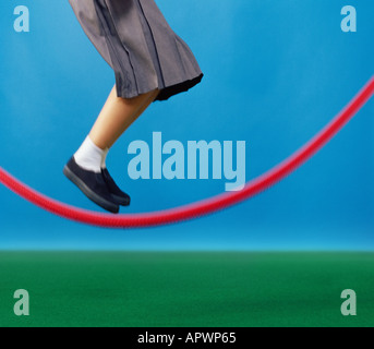 Girl jumping over skipping rope - Stock Photo