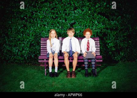 Schoolchildren on a bench - Stock Photo