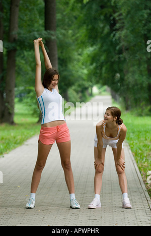 full body portrait of young women doing stretching exercises in park - Stock Photo