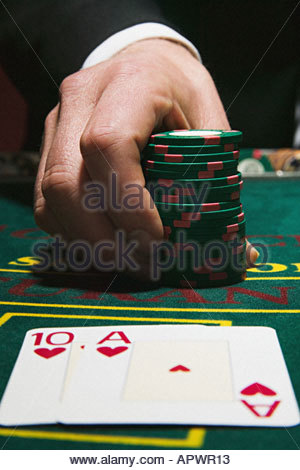 Man holding gambling chips with winning blackjack cards - Stock Photo