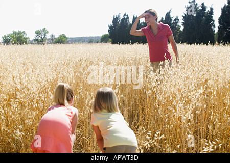 Mother and children playing hide and seek - Stock Photo