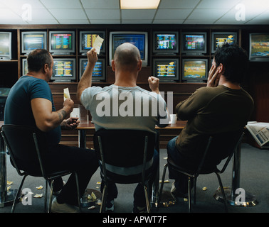 Three men in a betting shop - Stock Photo