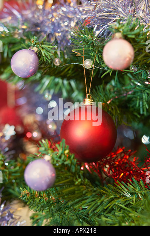 Christmas decorations with tinsel and red bauble - Stock Photo