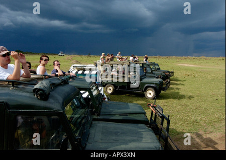 Tourists in several game viewing vehicles line up on the banks of the Mara River to watch the migration crossing - Stock Photo