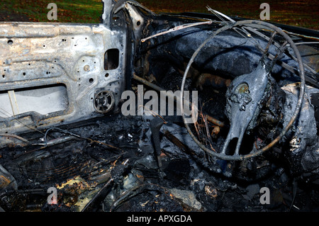 Abandoned burnt out car - Stock Photo
