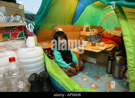 Homeless, living boxes in Tokyo, Japan, Homeless community on the banks of the Sumida River, young girl in the tent - Stock Photo