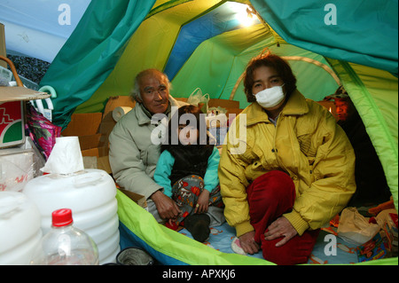 Homeless, living boxes in Tokyo, Japan, Homeless community on the banks of the Sumida River, young girl with parents - Stock Photo