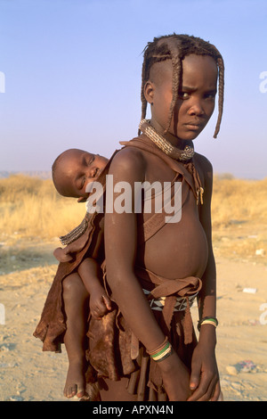Young Himba girl carries a little child on her back - Stock Photo