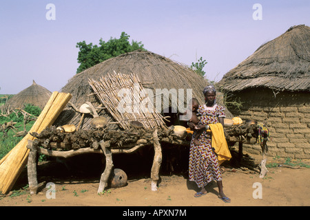 A young mother holding her child on her hip outside a thatched hut in a village near Tonka - Stock Photo