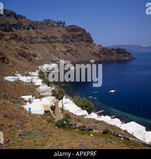 Looking down on Manolas harbour with donkeys on steep cliff path Thirasia Island off Santorini The Greek Islands - Stock Photo