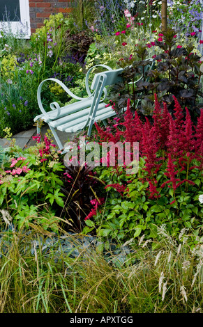 Seat in cottage garden surrounded by flowers including red astilbe, with house in background - Stock Photo