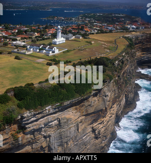 View along steep sheer ocean cliffs to Watsons Bay with Macquarie lighthouse on top and Sydney Harbour beyond Australia - Stock Photo