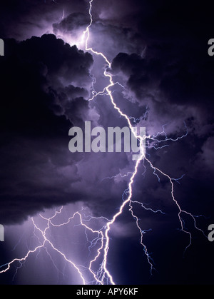 Lightning bolts strike dramatically from a dark and stormy sky. The clouds glow purple and are ominous against the - Stock Photo