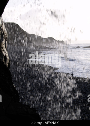 Looking out onto Sandymouth Beach , Cornwall , UK , British Isles through the falling water of a waterfall - Stock Photo