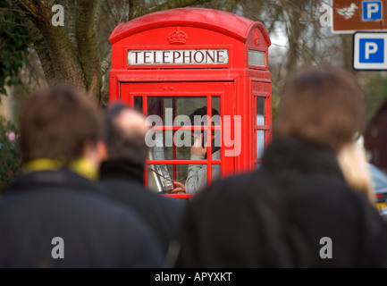 A young man using a red telephone box in a busy urban street. Picture by Jim Holden. - Stock Photo