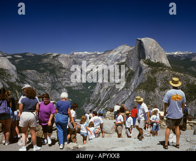 Tourist enjoy the view to the Half Dome viewed from Glacier Point, Yosemite NP, California, USA - Stock Photo