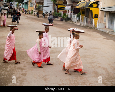 nuns walking on their morning alms rounds in the old city of Bagan in Myanmar - Stock Photo