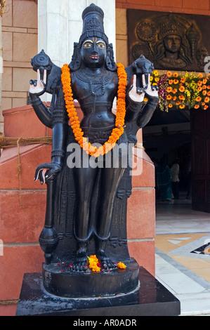 A bronze deity statue at Iskcon Hari Krishna Temple, Delhi, India - Stock Photo