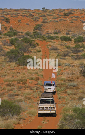 Convoy of 4WD in red sand dunes, travelling along the French Line, Simpson Desert, Queensland, Australia - Stock Photo