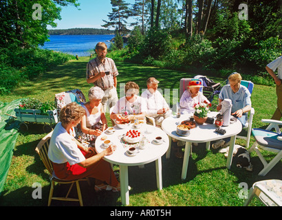 Friends sharing food, coffee and conversation on family owned island in Stockholm Archipealgo - Stock Photo