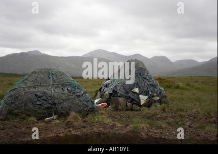 mounds of Turf peat cut in front of mountains in a peat bog in Connemara County Galway Republic of Ireland - Stock Photo