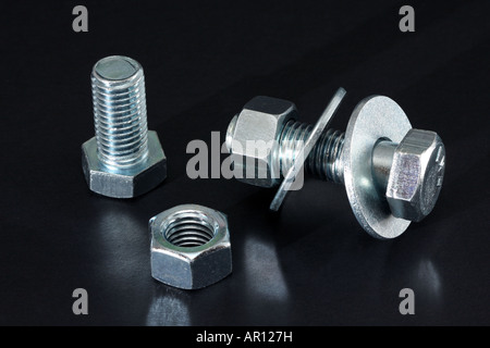 A line up of some large nuts and bolts with matching washers. - Stock Photo