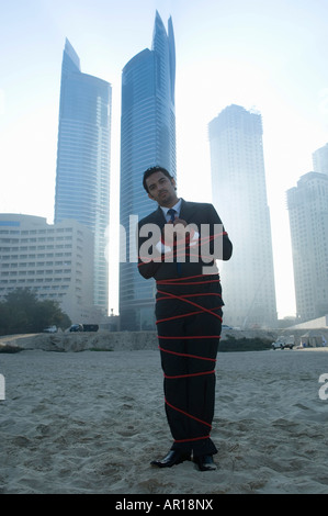Businessman tied with rope, towers seen through the mist in the background - Stock Photo