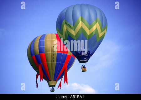 Two colorful hot air balloons in blue sky with clouds at Balloon festival Albuquerque NM - Stock Photo